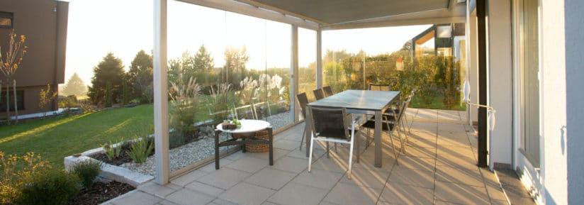 Table de jardin haut de gamme sous un coucher de soleil devant une maison luxueuse